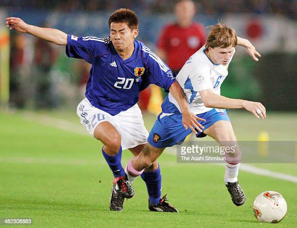 Tomokazu Myojin of Japan and Igor Semshov of Russia compete for the ball during the FIFA World Cup Korea/Japan Group H match between Japan and Russia...