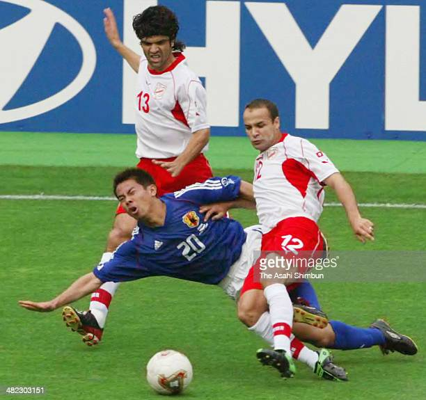 Tomokazu Myojin of Japan is tackled by Raouf Bouzaiene of Tunisia during the FIFA World Cup Korea/Japan Group H match between Tunisia and Japan at...