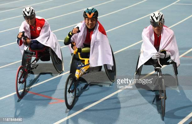 Tomoki Sato, Hirokazu Ueyonabaru and Tomoya Ito of Japan celebrate after the Men's 1500m T52 final race on Day Nine of the IPC World Para Athletics...