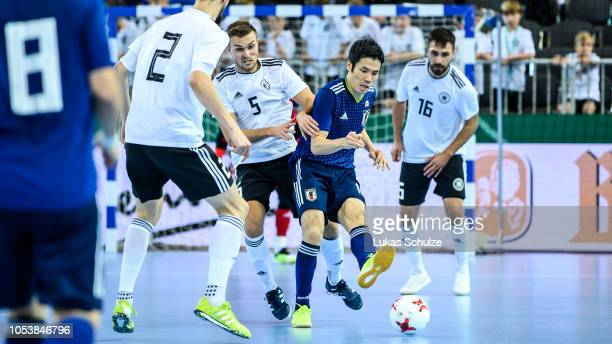 Tomoki Yoshikawa of Japan battles for possession with Jonas Hoffmann of Germany and Christoph Wittig of Germany during the futsal international...