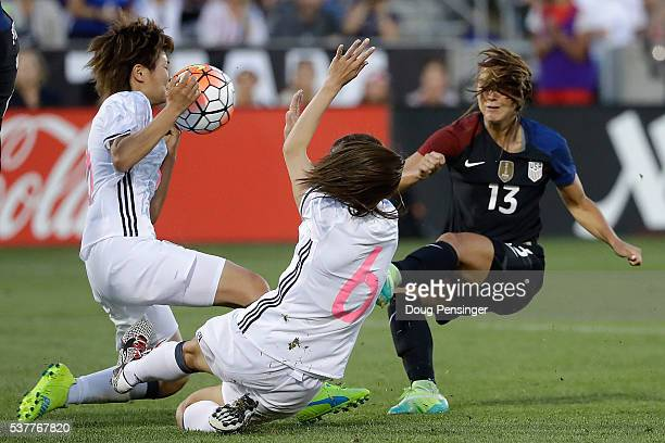Tomoko Muramatsu of Japan and Rumi Utsugi defend against a shot by Alex Morgan of United States of America during an international friendly match at...