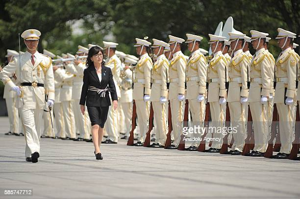 Tomomi Inada the newly appointed defense minister of Japan reviews a guard of honor during a welcoming ceremony at the Ministry of Defense in Tokyo...