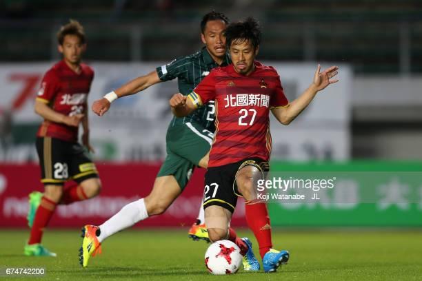 Tomonobu Hiroi of Zweigen Kanagawa controls the ball under pressure of Hiroaki Namba of FC Gifu during the JLeague J2 match between FC Gifu and...