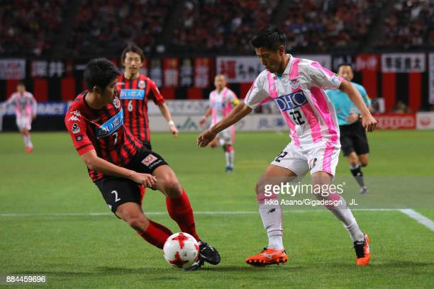 Tomonobu Yokoyama of Consadole Sapporo and Kei Ikeda of Sagan Tosu compete for the ball during the JLeague J1 match between Consadole Sapporo and...