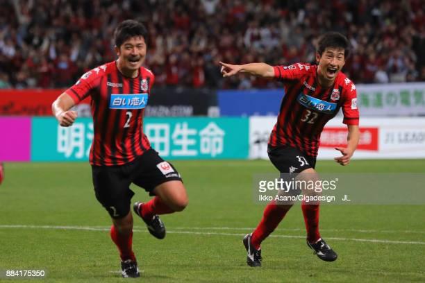 Tomonobu Yokoyama of Consadole Sapporo celebrates scoring his side's third goal with his team mate Naoki Ishikawa during the JLeague J1 match between...