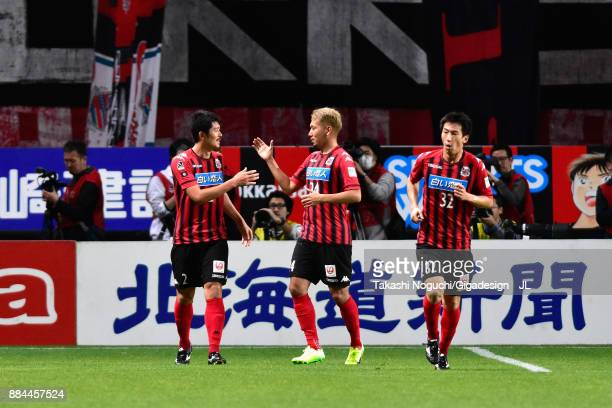Tomonobu Yokoyama of Consadole Sapporo celebrates scoring his side's third goal with his team mates Akito Fukumori and Naoki Ishikawa during the...