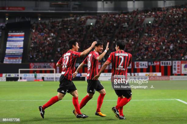Tomonobu Yokoyama of Consadole Sapporo celebrates scoring his side's third goal with his team mates Ryota Hayasaka and Naoki Ishikawa during the...