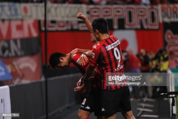 Tomonobu Yokoyama of Consadole Sapporo celebrates scoring his side's third goal with his team mate Ken Tokura during the JLeague J1 match between...