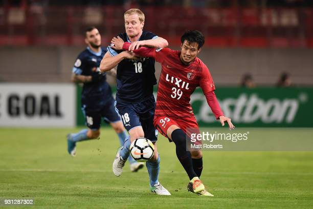Tomoya Inukai of Kashima Antlers competes for the ball against Matt Simon of Sydney FC during the AFC Champions League Group H match between Kashima...