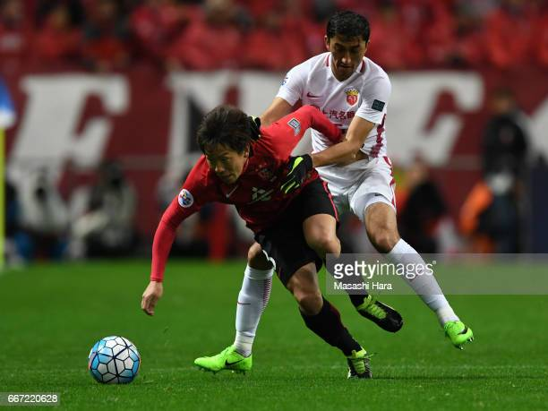 Tomoya Ugajin of Urawa Red Diamonds and Akhmedov Odil of Shanghai SIPG compete for the ball during the AFC Champions League Group F match between...