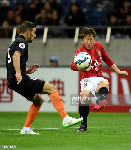 Tomoya Ugajin of Urawa Red Diamonds and Andrija Kaluderovic of Brisbane Roar compete for the ball during the AFC Champions League Group G match...