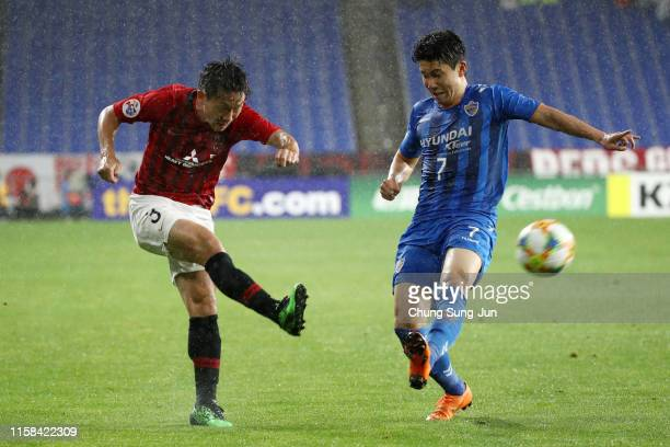 Tomoya Ugajin of Urawa Red Diamonds and Kim In-sung of Ulsan Hyundai compete for the ball during the AFC Champions League round of 16 second leg...