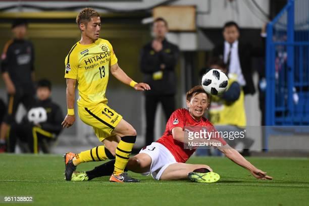 Tomoya Ugajin of Urawa Red Diamonds and Ryuta Koike of Kashiwa Reysol compete for the ball during the JLeague J1 match between Kashiwa Reysol and...