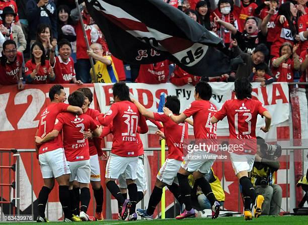 Tomoya Ugajin of Urawa Red Diamonds celebrates scoring the first goal with his team mates during the J.League match between Urawa Red Diamonds and...