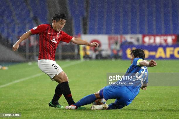 Tomoya Ugajin of Urawa Red Diamonds is tackled by Park Joo-ho of Ulsan Hyundai during the AFC Champions League round of 16 second leg match between...