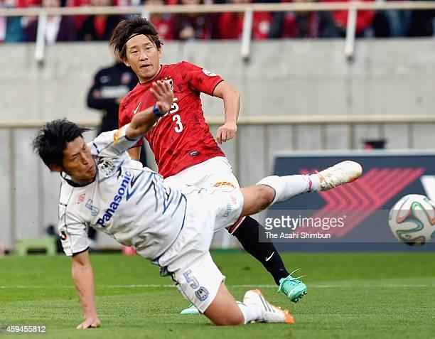 Tomoya Ugajin of Urawa Red Diamonds shoots while Daiki Niwa of Gamba Osaka attempts to block during the JLeague match between Urawa Red Diamonds and...