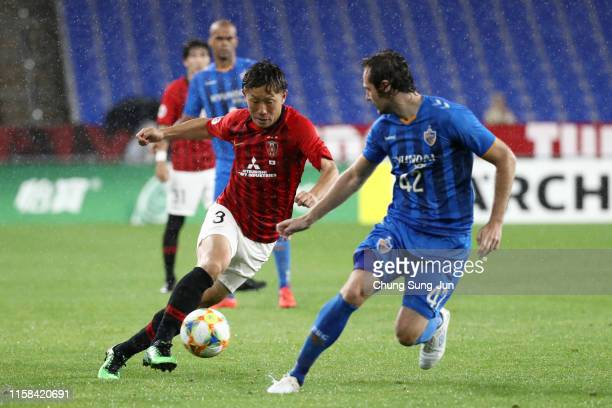 Tomoya Ugajin of Urawa Red Diamonds takes on Mix Diskerud of Ulsan Hyundai during the AFC Champions League round of 16 second leg match between Ulsan...