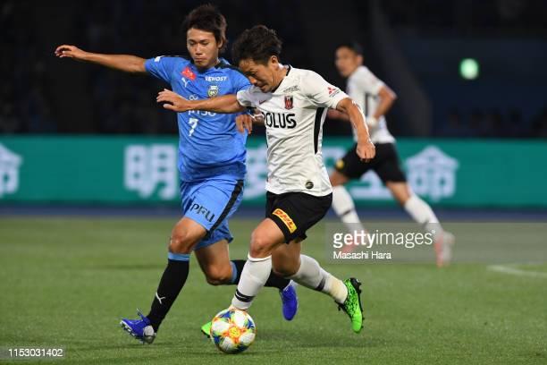 Tomoya Ugajin of Urawa Reds and Shintaro Kurumaya of Kawasaki Frontale compete for the ball during the J.League J1 match between Kawasaki Frontale...