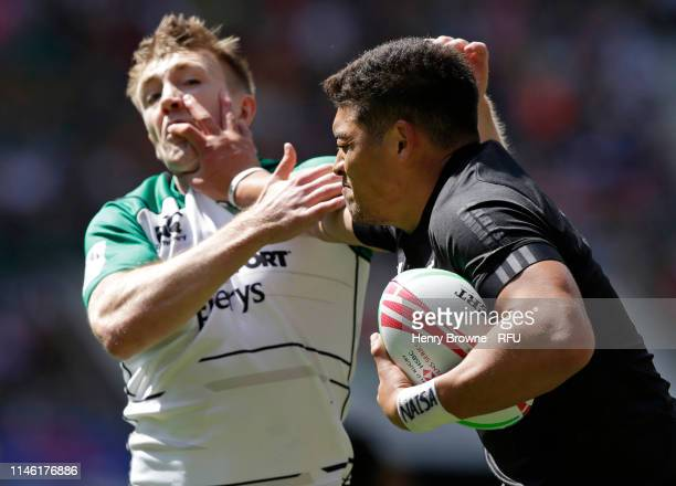 Tone Ng Shiu of New Zealand hands off Terry Kennedy of Ireland during the HSBC London Sevens match between New Zealand and Ireland at Twickenham...