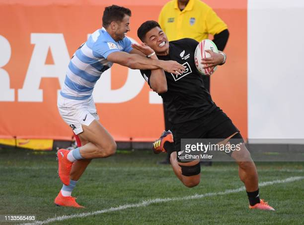 Tone Ng Shiu of New Zealand scores a try against Liam McNamara of Argentina during the USA Sevens Rugby tournament at Sam Boyd Stadium on March 3...