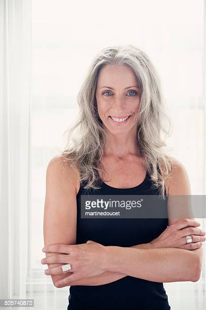toned and tanned mature woman with silver hair in tanktop. - white hair stock pictures, royalty-free photos & images