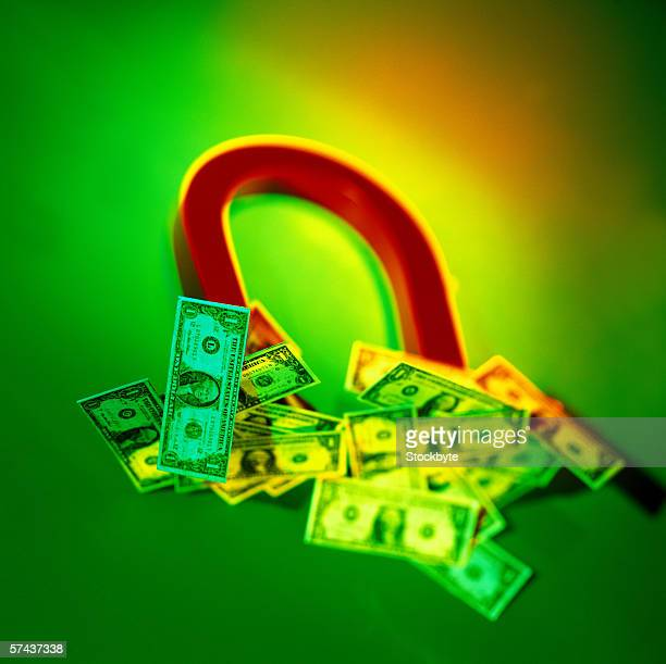 toned close-up of a horseshoe magnet with dollar bills attached to it - horseshoe magnet stock pictures, royalty-free photos & images