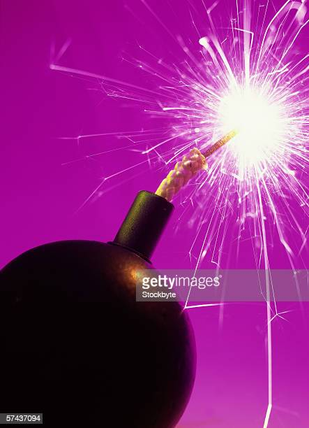 toned close-up of a lit time bomb - time bomb stock photos and pictures