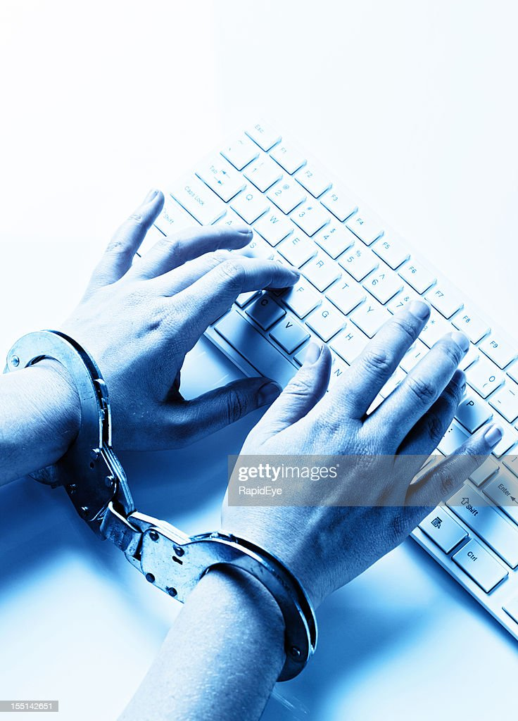 Toned image: looking down on handcuffed hands typing at computer : Stock Photo