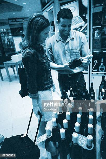 toned shot of a couple reading the label of a champagne bottle at the duty free shop