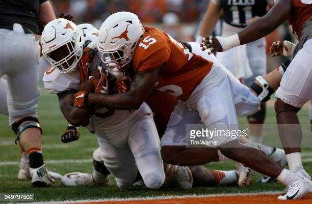 Toneil Carter of the Texas Longhorns loses his helmet sticker while being stopped short of the goal line by Chris Brown and Jamari Chisholm in the...