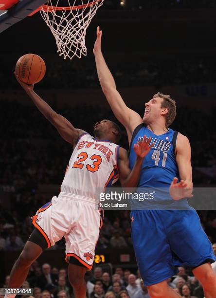 Toney Douglas of the New York Knicks lays the ball up under Dirk Nowitzki of the Dallas Mavericks at Madison Square Garden on February 2 2011 in New...