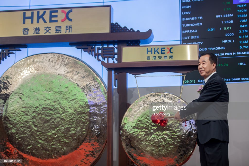Tong Jilu, chairman of China Tower Corp., poses for photographs in front of a gong during the company's listing ceremony at the Hong Kong Stock Exchange in Hong Kong, China, on Wednesday, Aug. 8, 2018. China Tower inched up in Hong Kong trading debut after completing the world's largest initial public offering in two years. Photographer: Paul Yeung/Bloomberg via Getty Images