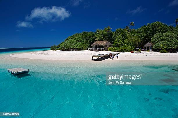 tongan beach with small wooden jetty and thatched huts. - tonga stock pictures, royalty-free photos & images