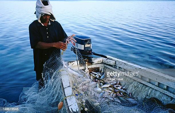 Tongan fisherman brings his days catch onto the boat, Atata Island near Nuku'alofa.