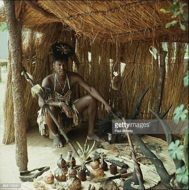 A Tongan shaman from Zambia sits in his grass hut with various gourds animal horns and other items spread before him