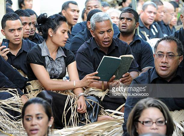 Tongans dressed in black for mourning and wearing the traditional ta'ovala waistmats sing for Queen Halaevala Mata'aho the mother of King George...