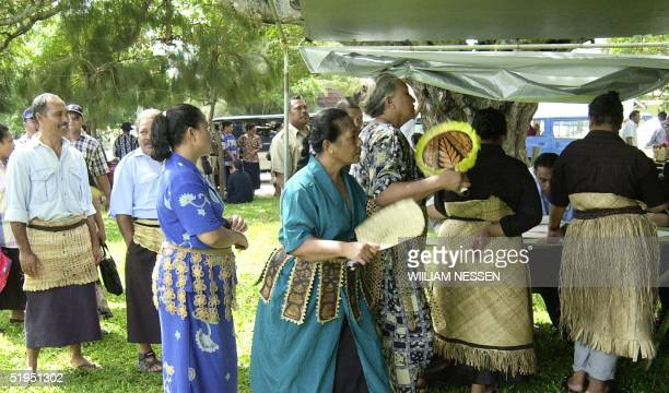 Tongans wearing traditional woven bark sarongs queue at a polling booth in the capital Nuku'alofa, 07 March 2002, during the Polynesian archipelago's...