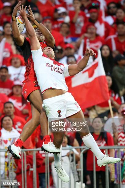 Tonga's David Fusitua and England's Ryan Hall compete for the high ball during the Rugby League World Cup men's semifinal match between Tonga and...