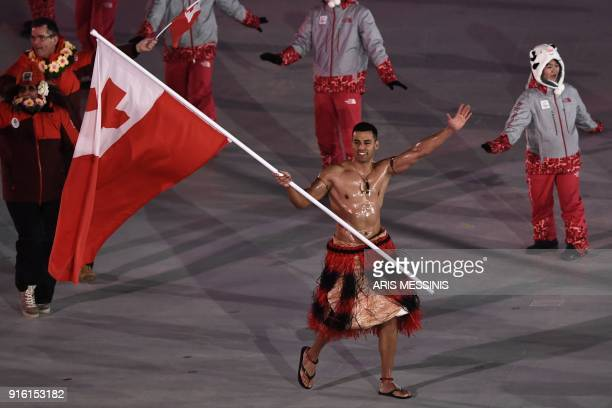 Tonga's flagbearer Pita Taufatofua leads his country's delegation as he parades in shirtless traditional attire better suited for the tropics during...