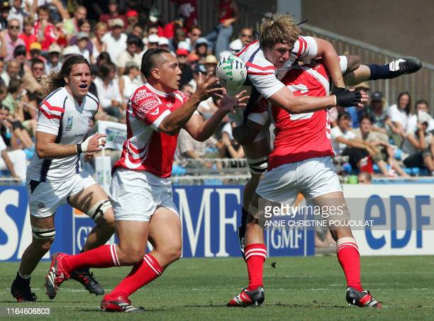 Tonga's fly-half Raymond Pierre Hola catches the ball as USA's prop Louis Stanfill is blocked by Tonga's flanker Hale T. Pole during the rugby union...