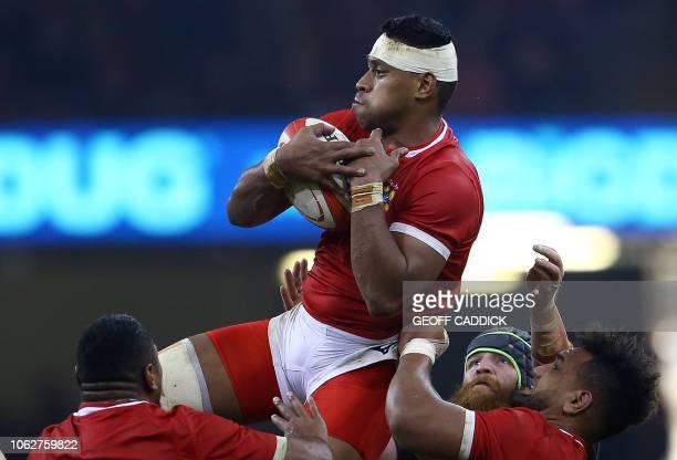 Tonga's hooker Paula Ngauamo and Tonga's number 8 Sione Vailanu lift Tonga's flanker Fotu Lokotui to catch the ball during the autumn international...