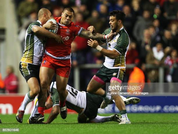 Tonga's Konrad Hurrell is tackled by Cook Island's Brad Takairangi John Zebelon Peyroux and Issac John during the the 2013 World Cup match at Leigh...