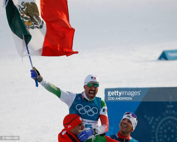 Tonga's Pita Taufatofua and Morocco's Samir Azzimani lift Mexico's German Madrazo onto their shoulders as they celebrate at the finish line in the...