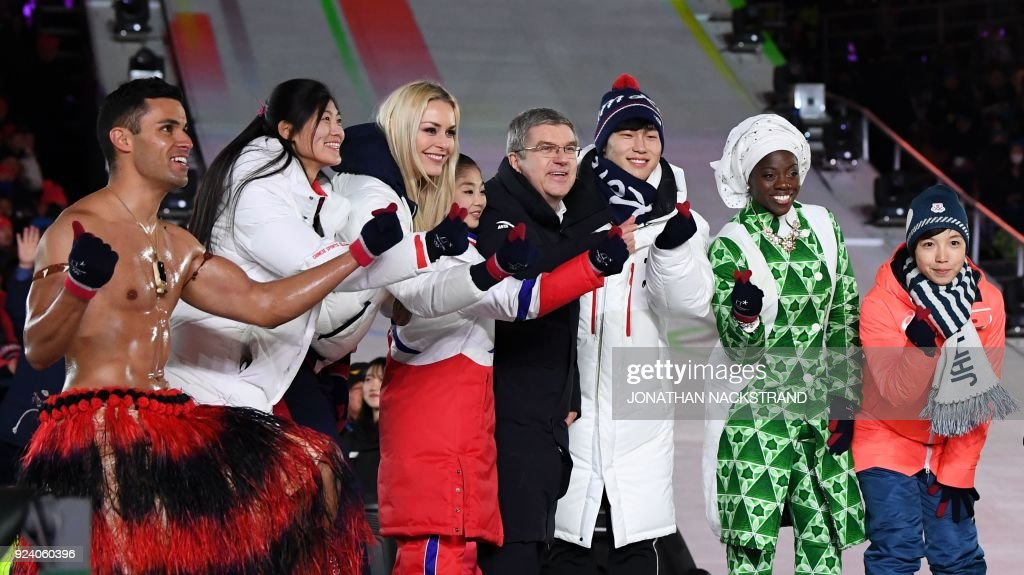 Tonga's Pita Taufatofua, China's Liu Jiayu, USA's Lindsey Vonn, North Korea's Kim Ju Sik, International Olympic Committee president Thomas Bach, South Korea's Yun Sungbin, Nigeria's Seun Adigun and Japan's Nao Kodaira make heart shapes with their fingers during the closing ceremony of the Pyeongchang 2018 Winter Olympic Games at the Pyeongchang Stadium on February 25, 2018. / AFP PHOTO / Jonathan NACKSTRAND