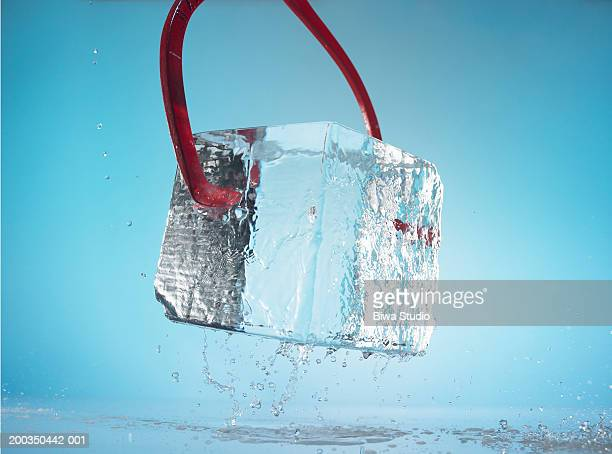 Tongs holding block of ice