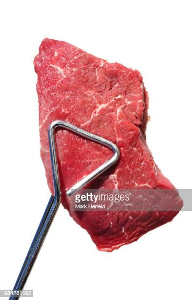 Tongs Holding Raw Beef Loin Top Sirloin Steak