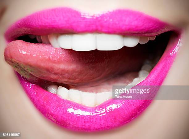 tongue licking pink lips - pink lipstick stock photos and pictures
