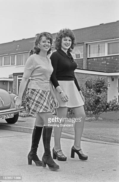 Toni and Shirlee Baxter wearing fashionable mini skirts and platform heels, UK, 26th October 1974.