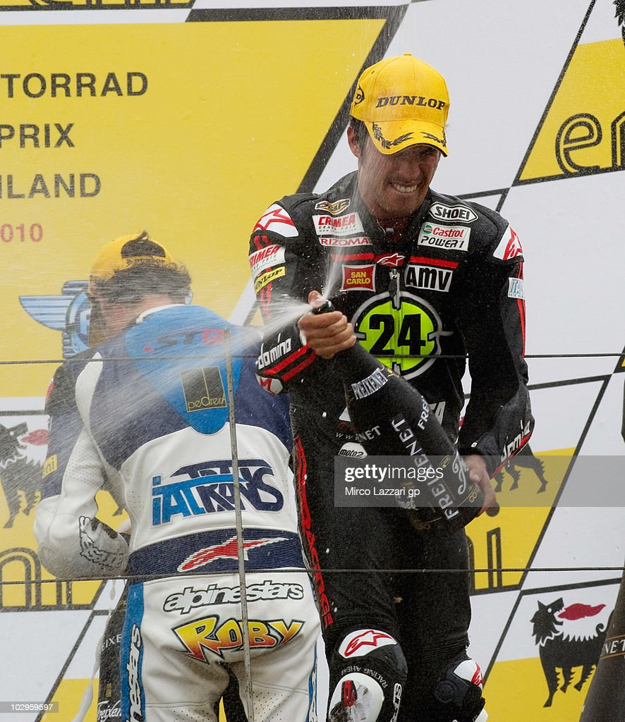 Toni Elias (in front) of Spain and Gresini Racing Moto2 and Roberto Rolfo of Italy and Italtrans S.T.R. spray champagne and celebrate on the podium at the end of the Moto2 race of Grand Prix of Germany at Sachsenring Circuit on July 18, 2010 in Hohenstein-Ernstthal, Germany.