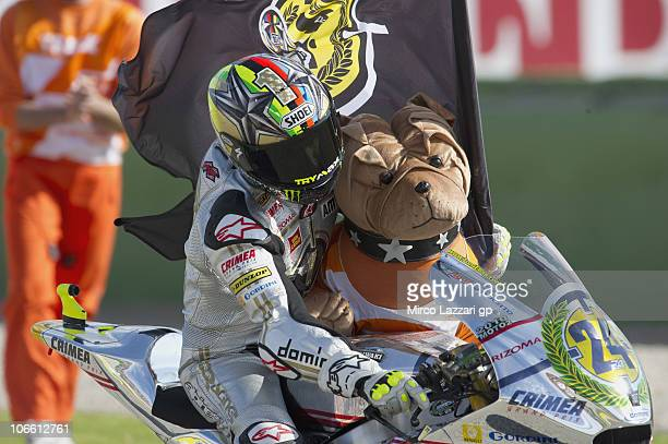 Toni Elias of Spain and Gresini Racing Moto2 celebrates the victory in the Moto2 Championship with the flag and a dog at the end of Moto2 of Valencia...